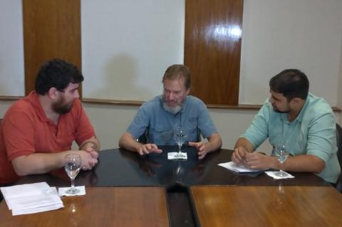Três homens sentados a uma mesa; dois deles, nas pontas, prestam atenção à fala do que está no centro