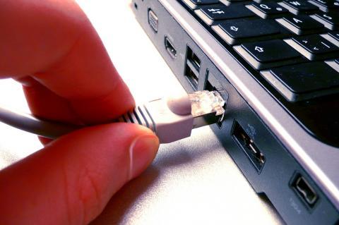 dedos plugando um cabo de internet