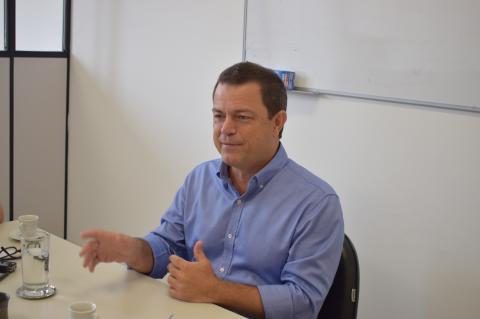 Homem de camisa social azul, sentado a uma mesa, fala e gesticula
