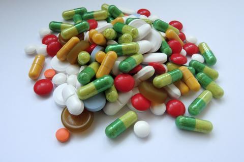 Comprimidos e cápsulas de vários formatos e cores espalhados