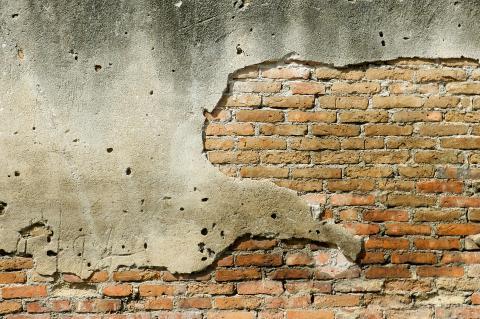 Muro descascando, deixando aparentes os tijolos