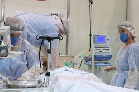 Profissional de saúde com equipamentos de proteção observa paciente monitorizado em leito hospitalar