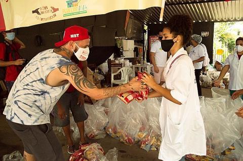 Homem de camiseta, boné vermelho e máscara recebe alimentos das mãos de uma mulher de jaleco e máscara,em meio a sacos com cestas básicas