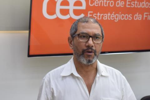 Homem de óculos e camisa branca, em primeiro plano, olha para frente e parece estar falando, tendo ao fundo tela de TV em cor laranja