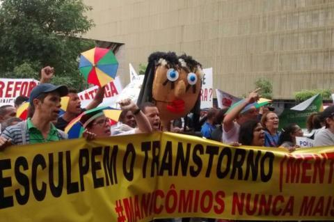 Manifestantes levam uma faixa amarela em primeiro plano, onde se lê: 'Desculpe o transtorno. #Manicômios nunca mais'