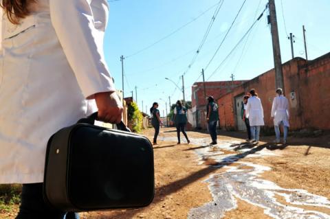 Detalhe em destaque de pessoa de costas, usando jaleco branco e carregando uma maleta em uma rua de terra, com pequenas casas