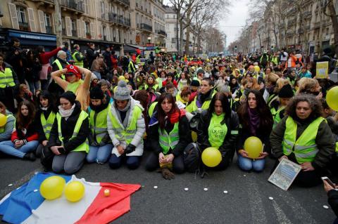 Pessoas agachadas, usando coletes amarelos em manifestação na rua, em Paris