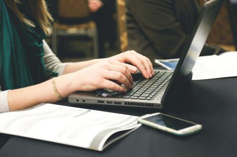 Mãos femininas teclam em um notebook, havendo ao lado uma apostila em papel aberta