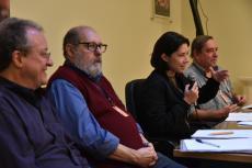 Mesa de debates, com os participantes em perspectiva, tendo em primeiro plano homem de óculos e blusa azul