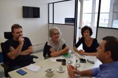 Duas mulheres e dois homens conversam sentados a uma mesa